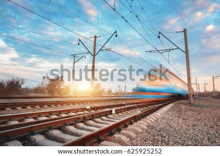 High speed blue passenger train in motion on railroad at sunset. Blurred commuter train. Railway station against colorful sky. Railroad travel, railway tourism. Rural industrial landscape. Vintage