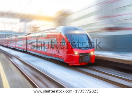 High speed double decker express train arrives at a station in the city