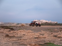 High-speed fast off-road buggy cars racing at waste land with big rocks in Ayia Napa, Cyprus. Hotel buildings at the background.