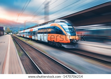 Photo of  High speed orange train in motion on the railway station at sunset. Modern intercity passenger train with motion blur effect on the railway platform. Industrial. Railroad in Europe. Transport