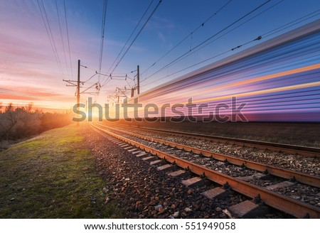 High speed passenger train in motion on railroad at sunset. Blurred commuter train. Railway station against sunny sky. Railroad travel, railway tourism. Rural industrial landscape. Concept #551949058