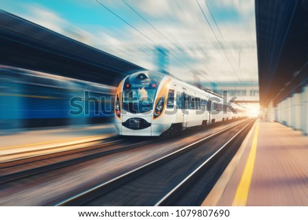 High speed passenger train in motion on the railway station at sunset in Europe. Modern intercity train on railway platform with motion blur effect. Urban scene with railroad. Railway transportation #1079807690