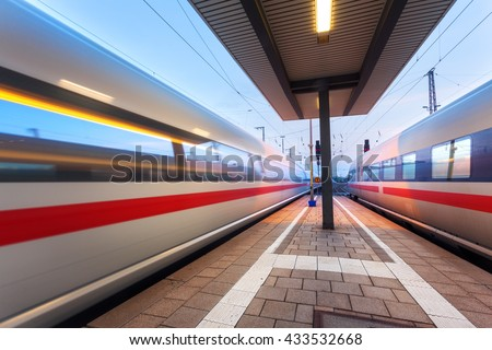 High speed passenger trains on railroad platform in motion at dusk. Blurred commuter train. Railway station in Nuremberg, Germany. Industrial landscape