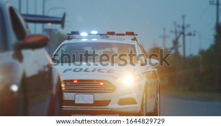 High speed police pursuit on highway. View of cop patrol car chasing a thief on red modern car driving away from the law. Foto stock ©