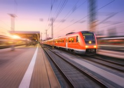 High speed red train with motion blur effect on the railway station at sunset. Landscape. Modern intercity passenger train in motion on the railway platform at dusk. Commuter vehicle on railroad