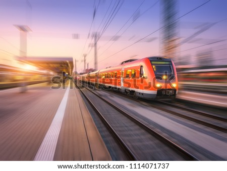 High speed red train with motion blur effect on the railway station at sunset. Landscape. Modern intercity passenger train in motion on the railway platform at dusk. Commuter vehicle on railroad #1114071737