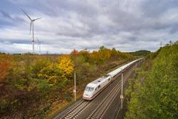 high speed train crosses several wind turbines