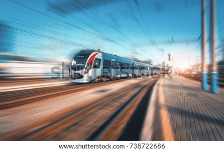 High speed train in motion at the railway station at sunset in Europe. Modern intercity train on railway platform with motion blur effect. Industrial landscape. Passenger train on railroad. Vintage #738722686