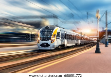 High speed train in motion at the railway station at sunset. Modern european intercity train on the railway platform with motion blur effect. Industrial scene with moving passenger train on railroad #658551772