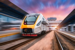 High speed train in motion on the railway station at sunset. Fast moving modern passenger train on railway platform. Railroad with motion blur effect. Commercial transportation. Front view. Concept