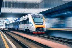 High speed train in motion on the railway station at sunset. Modern intercity passenger train with motion blur effect on the railway platform. Industrial. Railroad in Europe. Transportation. Industry