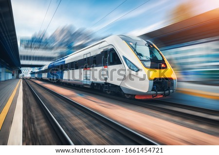 High speed train in motion on the railway station at sunset. Modern intercity passenger train with motion blur effect on the railway platform. Industrial. Railroad in Europe. Commercial transportation