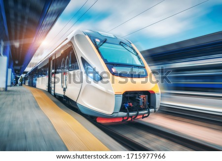 High speed train in motion on the railway station at sunset. Modern intercity passenger train with motion blur effect on the railway platform. Industrial. Railroad in Europe. Commercial transportation stock photo