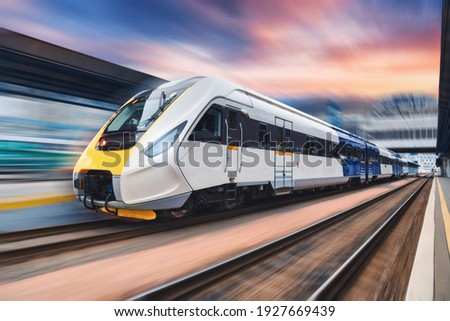 High speed train in motion on the railway station at sunset. Modern intercity passenger train with motion blur effect on the railway platform. Industrial. Railroad transportation in Europe Foto stock ©