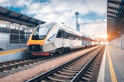 High speed train on the railway station at sunset. Industrial landscape with modern intercity passenger train on the railway platform and blue cloudy sky. Railroad in Europe. Commercial transportation