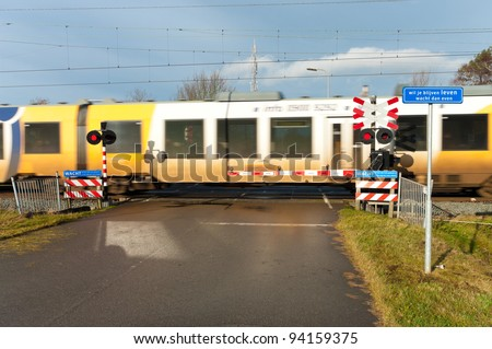 "high speed train passing a secured railway crossing. The blue shield says ""If you want to stay alive, you better wait a minute""."