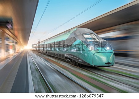 High speed train passing near the passenger station in the city.