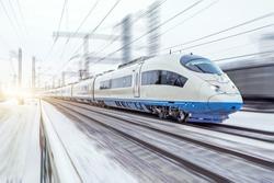 High-speed train rides at high speed in winter around the snowy landscape