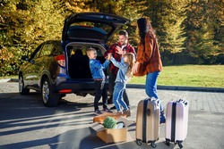 High-spirited likable parents unloading the auto's trunk with their cute 10-12s kids during moving into new apartment.