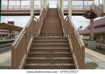 High stairs to bridge for railway crossing at train station #1494524837