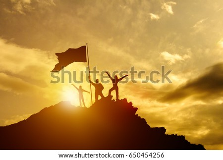 High success, family three silhouette, father of mother and child holding flag of victory on top of mountain, hands up. man on top of a mountain. Conceptual design. Against the dramatic sky at sunset #650454256