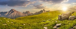 High Tatra mountain summer landscape. meadow with huge stones among the grass on top of the hillside near the peak of mountain range at sunset