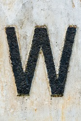 high texture letter W in black peeling paint on white background