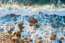High tide on a rocky beach at sunset