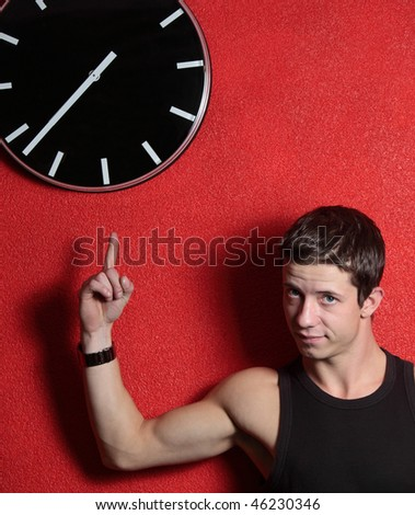 High time concept - casual handsome young man pointing at a ticking clock on a red wall