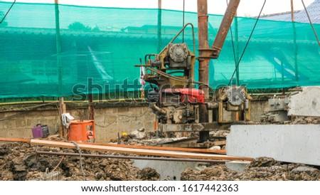high tripod steel machine construction in site  piling equipment. Building house.  three legs metal steel crane.