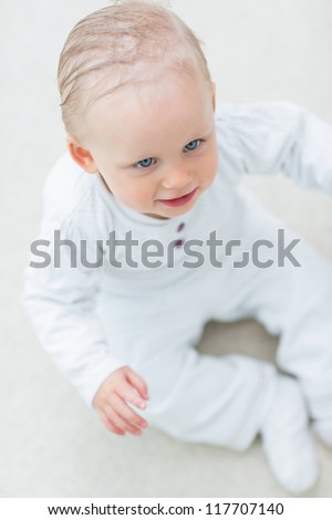 High view of a baby sitting on the floor in living room