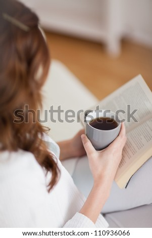 High view of a woman holding a mug coffee in a living room