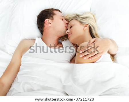 High view of boyfriend kissing her girlfriend in bed