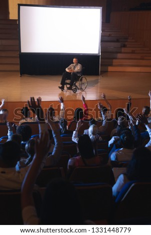 High view of Caucasian businessman sitting on a wheelchair and giving presentation to the audience while audience raising hand for asking question in auditorium #1331448779