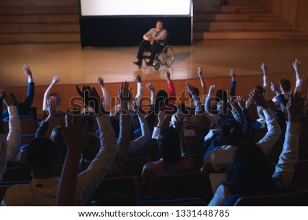 High view of Caucasian businessman sitting on a wheelchair and giving presentation to the audience while audience raising hand for asking question in auditorium #1331448785