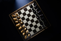 High view of chess pieces on a chessboard in a dark style.