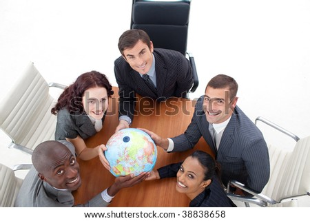 High view of happy business people holding a globe in a meeting. Global business