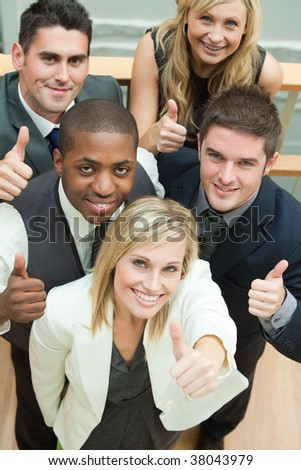 High view of happy business team with thumbs up and smiling at the camera