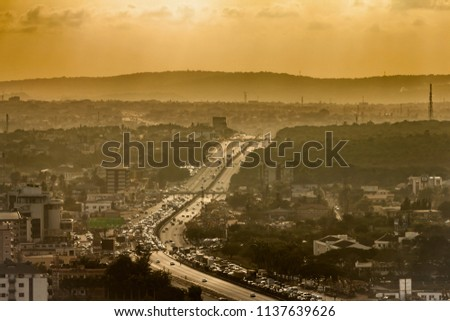 High view point hazy cityscape of Accra, Ghana. Traffic jam on George Bush Highway with hills on the background