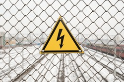 High voltage danger warning sign on the fence above the railroad.