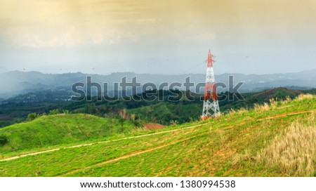 High voltage electric tower on green field with mountains in rural Produce electricity to supply electricity to industrial in city in the evening time.  #1380994538