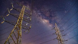 High voltage electric tower on milky way sky background, High voltage electricity pylon and transmission power line and a Parts of electrical equipment and high voltage power line insulators at night