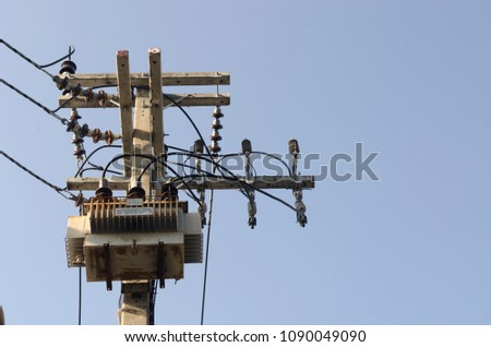 High voltage electric transformer in a power substation above the tower.