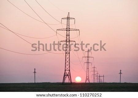 High-voltage electric transmission line silhouette against the setting sun
