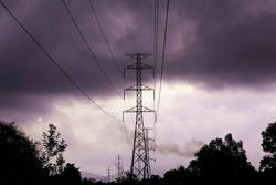 High voltage electricity distribution pole with trees shadow, Electricity pole against with storm clouds, Electric supply transmission pylon line for energy generator technology industry