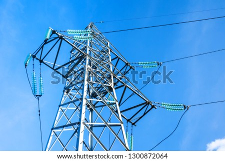 High voltage electricity pylon and transmission power line on the blue sky and white clouds on the background. Parts of electrical equipment and high voltage power line insulators.