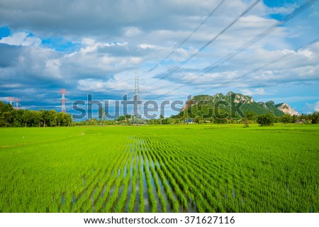 High voltage electricity pylon on the confield have mountain and sky on background - Shutterstock ID 371627116