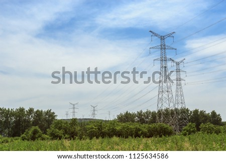High voltage electricity tower under cloudy blue sky #1125634586