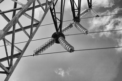 High-voltage line for the transmission of electrical energy. The glass insulators are photographed against a cloudless blue sky