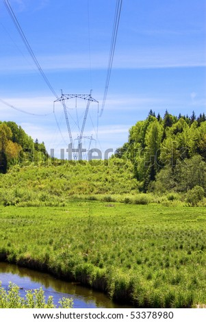 High-voltage line of electricity transmissions in Field among wood on riverside
